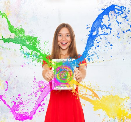 Photo for Happy smiling girl holding tablet screen with splashing colorful paint - Royalty Free Image