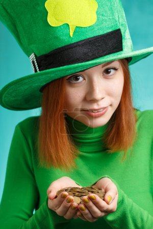 Red hair girl in Saint Patrick's Day leprechaun party hat with g