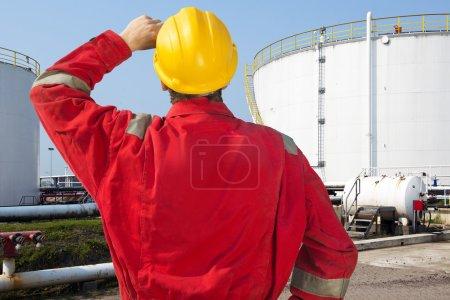 Foto de Ingeniero de petróleo mirando atrasadas cuestiones de mantenimiento y seguridad de tanques de almacenamiento con la fuente de petróleo crudo - Imagen libre de derechos