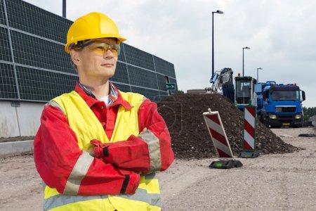 Photo pour Travailleur de la construction routière, vêtu d'un gilet de sécurité et d'autres précautions de sécurité, surplombant le chantier, avec un camion à benne et une pelleteuse en arrière-plan - image libre de droit