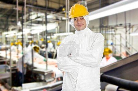 Photo pour Souriant travailleur dans une abattoir et l'usine de transformation de la viande, porter des vêtements hygiéniques - image libre de droit