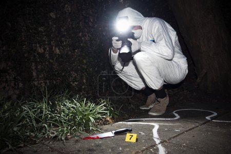 Photo for Forensics researcher photographing a blood stained knife at a murder scene - Royalty Free Image