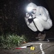 Forensics researcher photographing a blood stained...