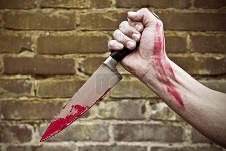 Photo pour Poing, tenant un sang souillé couteau, poignardant - image libre de droit