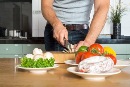 Midsection Of Man Cutting Vegetables