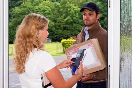 Photo for Young woman pays her cash on delivery parcel to a delivery postal worker using a portable, wireless ATM - Royalty Free Image