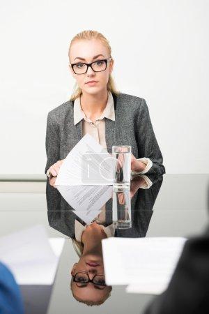 Photo pour Demandeur d'emploi au cours de son entrevue, avec son curriculum vitae devant elle - image libre de droit