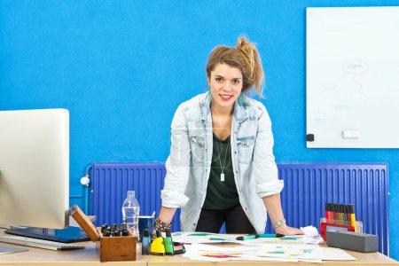 Photo pour Jeune designer de produits debout derrière son bureau, penché sur plusieurs croquis de produits, souriant à la caméra - image libre de droit