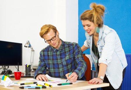 Photo pour Deux designers créatifs, travaillant sur une innovation produit, développant des idées et réfléchissant ensemble derrière un bureau dans un studio de design - image libre de droit