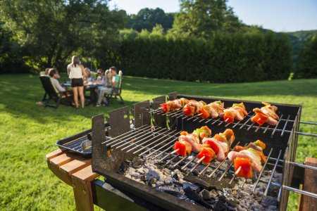Photo for Shlashlick laying on the grill with a group of friends in the background eating and drinking in the late sunny afternoon - Royalty Free Image