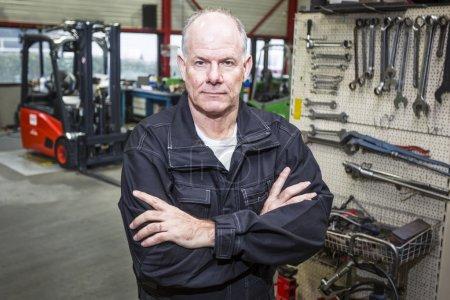 Photo pour Le mécanicien de chariot élévateur est confiant dans le garage avec un mur d'outils et le chariot élévateur en arrière-plan - image libre de droit