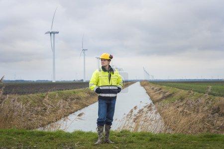 Photo pour Développeur de projet a des idées sur le paysage dans lequel il se trouve avec beaucoup de moulins à vent pour l'énergie verte en arrière-plan . - image libre de droit