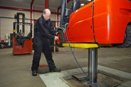 Photo pour Mécanicien, travaillant sur un chariot élévateur à fourche, le préparant pour le service après-vente, pneus de refroidissement . - image libre de droit