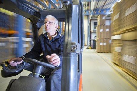 Photo pour Vue d'ensemble d'un conducteur de chariot élévateur, conduisant son véhicule à travers un entrepôt, avec un vaste flou de mouvement en arrière-plan - image libre de droit