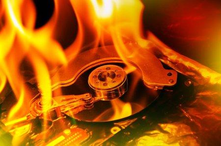 Foto de Cerrar imagen de disco duro de ordenador en fuego, que arde en flasmes. - Imagen libre de derechos