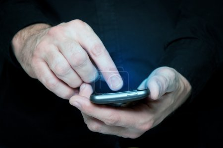 Photo for Man in black shirt is typing a text message on his smartphone, close up image, focus on hands and the phone device. - Royalty Free Image