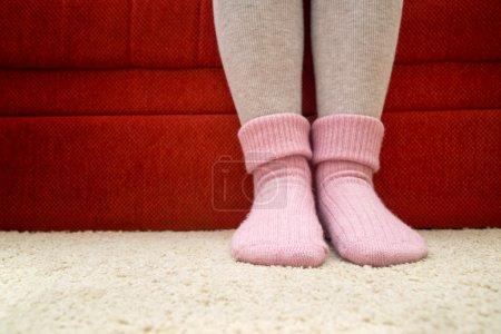 Photo pour Jambes féminines portant de belles chaussettes en laine rose chaud à la maison . - image libre de droit
