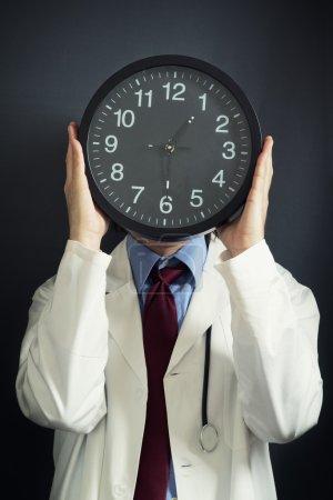 Photo pour Médecin tient des heures supplémentaires, une horloge noire en pf avant sa tête. travailler des heures supplémentaires, pas assez temps, la pression du temps, la notion de délai. - image libre de droit