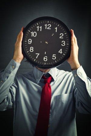 Photo pour Homme d'affaires avec horloge noire devant sa tête, concept de date limite. Pas assez de temps pour finir le travail . - image libre de droit
