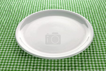 Photo for Empty white plate on kitchen table covered with checkered tablecloth. - Royalty Free Image