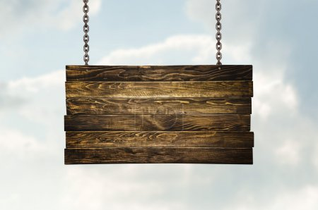Photo for Wooden signpost hanging on chains over white clouds - Royalty Free Image