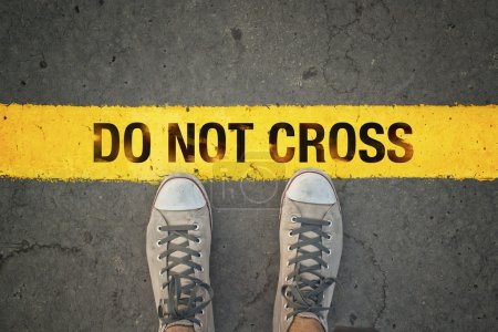 Photo for Man in sneakers standing at the yellow line with Do Not cross message - Royalty Free Image