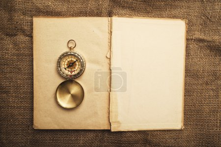 Photo for Vintage open book with old navigation compass. - Royalty Free Image