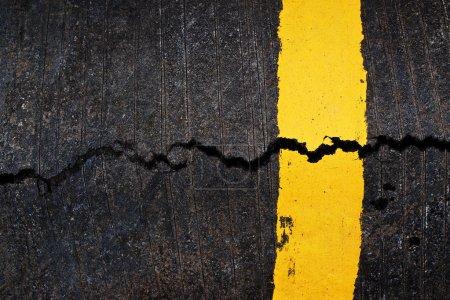 Yellow line on cracked asphalt road