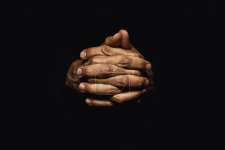 Photo for Male hands crossed for prayer in dark - Royalty Free Image