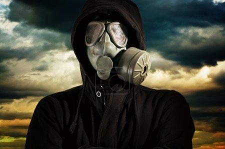 Photo pour Homme avec masque à gaz contre ciel dramatique avec de lourds nuages . - image libre de droit