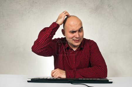 Photo for Confused man sitting at office table in front of the computer keyboard. Computer problem. - Royalty Free Image