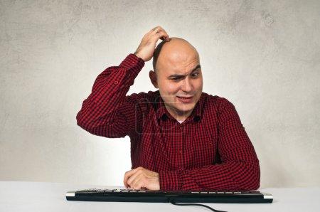 Photo pour Confondre l'homme assis à table devant le clavier de l'ordinateur du bureau. problème informatique. - image libre de droit