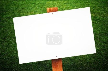 Photo pour Panneau blanc sur pelouse verte pour votre message . - image libre de droit