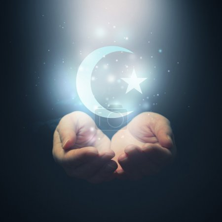 Female hands opening to light and Halh moon and star, symbol of