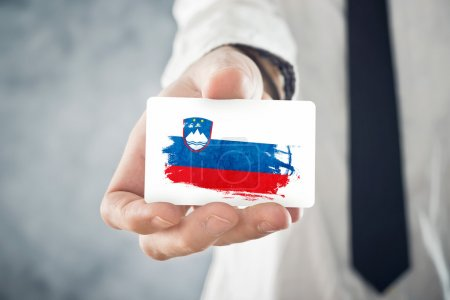 Slovenian Businessman holding business card with Slovenia Flag