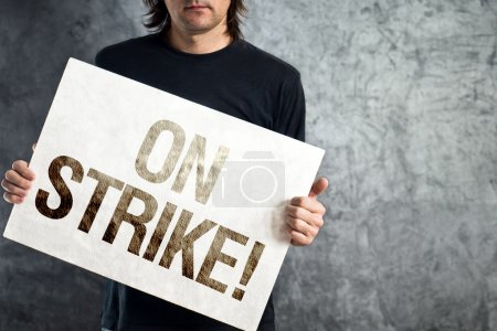 Worker on strike, man holding poster with printed protest messag