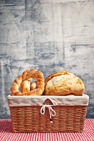 Photo for Delicious bread and rolls in wicker basket on kitchen table with copy space - Royalty Free Image