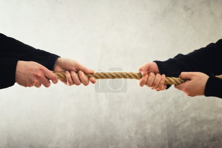Tug of war. Hands pulling rope to opposite sides