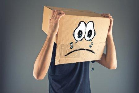 Photo pour Homme avec une boîte en carton sur la tête et l'expression du visage qui pleure triste. concept de la tristesse et la dépression. - image libre de droit