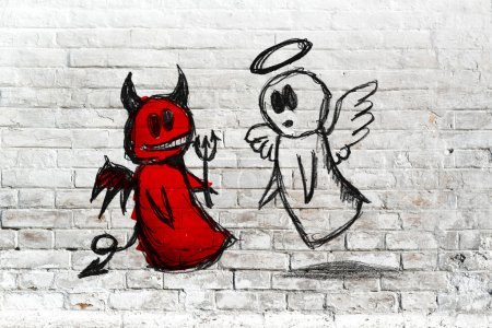 Angel and devil fighting - doodle drawing on white brick wall