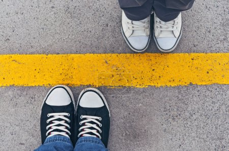 Photo for Sneakers from above. Male and female feet in sneakers from above, standing at dividing line. - Royalty Free Image