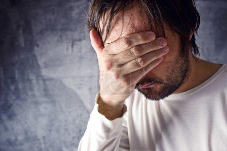Photo pour Dépressif homme pleurer avec main couvrant son visage, à la recherche de maux et affichage de remords - image libre de droit