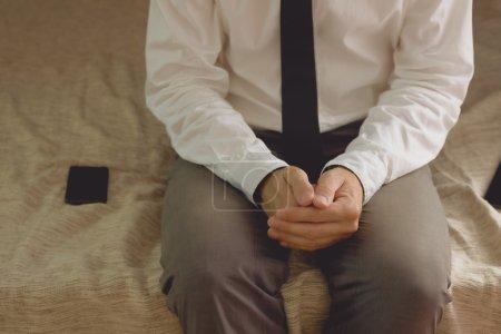 Photo pour Solitaire homme d'affaires dans la chambre d'hôtel assis sur le lit avec les mains croisées - image libre de droit