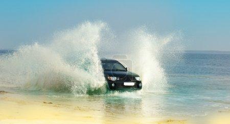 Photo pour Voiture de vitesse à travers les eaux peu profondes sur une plage plate - image libre de droit