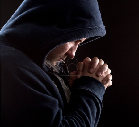 Photo for Despair bandit praying God for forgiveness - Royalty Free Image