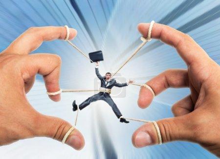 Photo pour Homme d'affaires stressé gouverné par des mains marionnettistes - image libre de droit