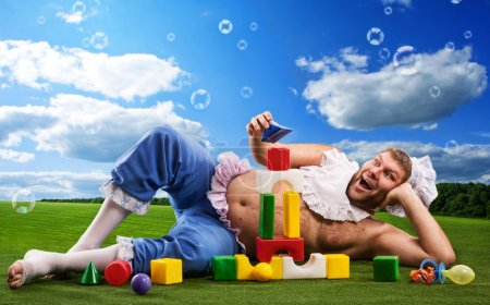 Photo pour Homme heureux porté comme bébé joue sur une prairie - image libre de droit