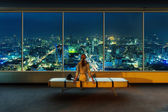 Woman looks at night cityscape