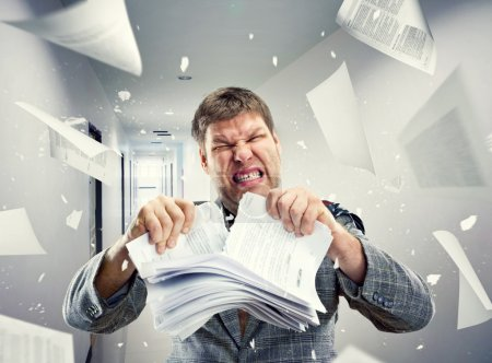 Photo for Stressed businessman tearing out stack of paper at office - Royalty Free Image