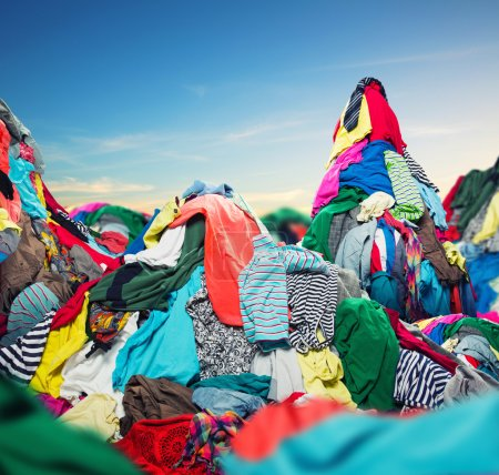 Photo for Big heap of colorful clothes on sky background - Royalty Free Image